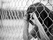Emotions concept - sadness, sorrow, melancholy. Portrait black and white sad boy behind fence mesh netting. Emotions concept - sadness, sorrow, melancholy royalty free stock image