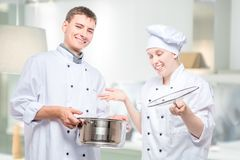 Emotions of cooks, portrait with soup pot on the background. Of a commercial kitchen royalty free stock photos