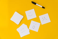 Emotions drawn on white sheets of paper are laid out on a yellow background.  Stock Photos