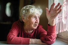 Emotions of elderly woman sitting at the table. royalty free stock images