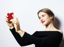 Emotions, expressions and people concept - happy smiling young woman wearing black dress  taking selfie with smartphone. Over white background Royalty Free Stock Image