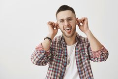 Emotions and feelings concept. Charming playful guy in stylish outfit and glasses pulling ears and sticking out tongue stock image