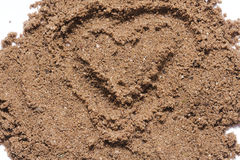 Emotions. Heart painted with fingers in sand stock photo