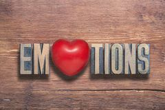Emotions heart wooden. Emotions word combined on vintage varnished wooden surface with heart symbol inside royalty free stock images