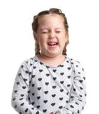 Emotions. The little curly girl shows that it hurts. White isolated background. Emotions. A little curly girl in a gray jacket with hearts shows that it hurts Royalty Free Stock Images