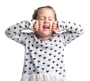 Emotions. The little girl stretches and yawns. White isolated background. Emotions. A little curly girl stretches and yawns in a gray sweater and red nails on Stock Photo