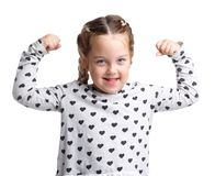 Emotions. Little girl shows biceps. White isolated background. Emotions. The little girl smiles and shows the biceps on two hands in a gray jacket with hearts Stock Photos