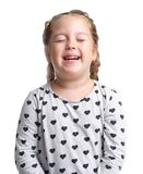 Emotions. The little girl is smiling. White isolated background. Emotions. Little girl smiles with closed in a gray sweater. White isolated background Royalty Free Stock Image