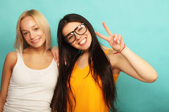 Emotions, people, teens and friendship concept - two young teen. Emotions, people, teens and friendship concept - two beautiful young teen girl giving victory Royalty Free Stock Photography