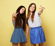 Emotions, people, teens and friendship concept - two young teen. Emotions, people, teens and friendship concept - two beautiful young teen girl giving victory Royalty Free Stock Images