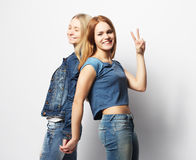 Emotions, people, teens and friendship concept - two young teen. Emotions, people, teens and friendship concept - two beautiful young teen girl giving victory Stock Images