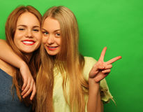Emotions, people, teens and friendship concept - two young teen. Emotions, people, teens and friendship concept - two beautiful young teen girl giving victory Stock Photos