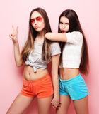 Emotions, people, teens and friendship concept - two young teen. Emotions, people, teens and friendship concept - two beautiful young teen girl giving victory Stock Photography