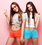Emotions, people, teens and friendship concept - two young teen. Emotions, people, teens and friendship concept - two beautiful young teen girl giving victory Stock Image