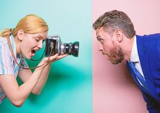 Emotions through photos. Businessman posing in front of female photographer. Pretty woman using professional camera stock images