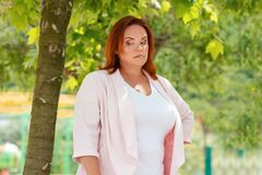 Free Emotions. Portrait Of A Plus-size Woman Showing Her Frustration And Discontent. In The Background Green Foliage Of Trees Stock Photography - 186488982