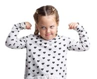 Emotions. Serious little curly girl. White isolated background. Emotions. A serious little curly girl shows her biceps on two hands. White isolated background Royalty Free Stock Photography
