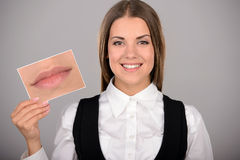 Emotions. Woman holding picture with big smile. concept photo over gray background Stock Photo