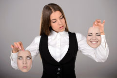 Emotions. Young businesswoman holding two masks with different emotions to choose from today. Gray background Royalty Free Stock Photos
