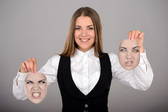 Emotions. Young businesswoman holding two masks with different emotions to choose from today. Gray background Royalty Free Stock Image