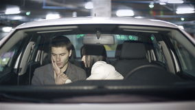 Emotions of a young couple in the car in the underground parking stock video