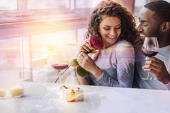 Wonderful couple being in love. Emotions. Young pleasant girl looking down while her boyfriend holding a glass of wine and looking at her with love royalty free stock photography