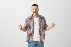Emotive adult in glasses and plaid shirt shouting fearfully and squeezing raised fists, being very excited of his royalty free stock photo