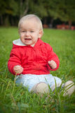 Emotive baby sit on green grass Royalty Free Stock Photos
