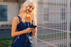 Emotive blond attractive girl in sunglasses with phone in summer sunshine urban stock photo