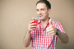 Emotive boy drinking and showing ok. Happy blue-eyed hipster boy drinking and showing thumb up over wooden background Stock Images