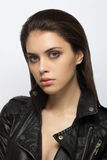Emotive closeup portrait of a young attractive brunette woman posing for model tests in black leather jacket Royalty Free Stock Photography