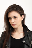 Emotive closeup portrait of a young naughty attractive brunette woman posing for model tests in black leather jacket Stock Image