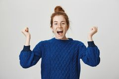 Emotive girl celebrates victory of her soccer team. Studio shot of expressive attractive woman with red hair and. Freckles shouting from happiness and shaking Stock Photo