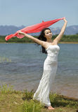 An emotive girl in field. An emotive girl is standing in field in evening dress  and waving red kerchiev extended in breeze Stock Photo