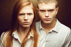 Emotive portrait of angry gorgeous red-haired fashion twins. In white shirts posing over golden background together. Close up. Studio shot royalty free stock photos