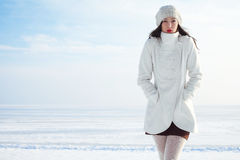 Emotive portrait of fashionable model in white coat and beret. Emotive portrait of a fashionable model in white coat and beret posing at the winter seaside stock image