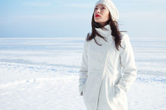 Emotive portrait of fashionable model in white coat and beret. Emotive portrait of a fashionable model in white coat and beret posing at the winter seaside Stock Photography