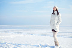 Emotive portrait of fashionable model in white coat and beret. Emotive portrait of a fashionable model in white coat and beret standing at the winter seaside royalty free stock images