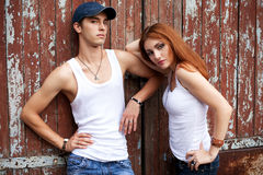 Emotive portrait of a stylish couple in jeans standing near wood Stock Images