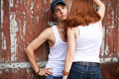 Emotive portrait of a stylish couple in jeans standing near wood Stock Photos