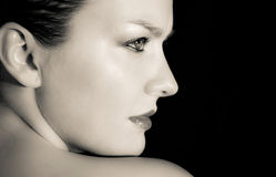 Emotive portrait of a young woman. With naked shoulder on black background Royalty Free Stock Photos