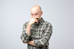 Emotive positive mature male covering mouth to stop laughter or hide smile, hearing or seeing something hilarious. While standing over gray background royalty free stock images