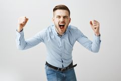 Emotive thrilled concerned european male boss in formal blue shirt and jeans bending towards camera yelling and raising. Fists cheering for football team making stock photos