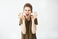 Emotive young attractive girl gesturing shouting looking at camera over white background. Copy space Royalty Free Stock Photo