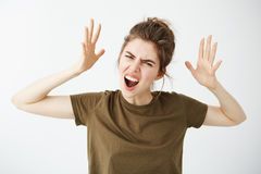 Emotive young attractive girl gesturing shouting looking at camera over white background. Copy space Stock Photo