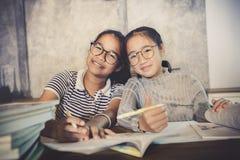 Emozione asiatica di felicità dell'adolescente che fa il lavoro della casa della scuola immagini stock