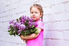 Emozioni del ` s dei bambini Bambino felice con un mazzo del lillà in sue mani Immagine Stock
