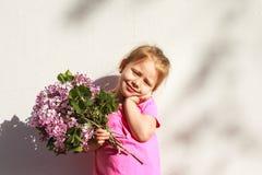 Emozioni del ` s dei bambini Bambino felice con un mazzo del lillà in sue mani Fotografia Stock Libera da Diritti