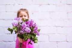 Emozioni del ` s dei bambini Bambino felice con un mazzo del lillà in sue mani Immagine Stock Libera da Diritti