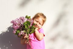 Emozioni del ` s dei bambini Bambino felice con un mazzo del lillà in sue mani Immagini Stock
